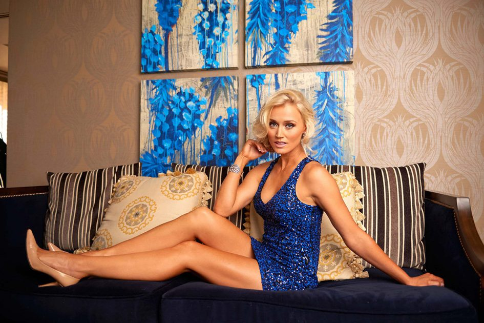 Blair O'Neal on a couch in a blue dress
